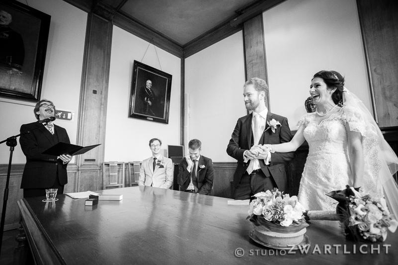 zwart-wit schaterlach tijdens huwelijksvoltrekking