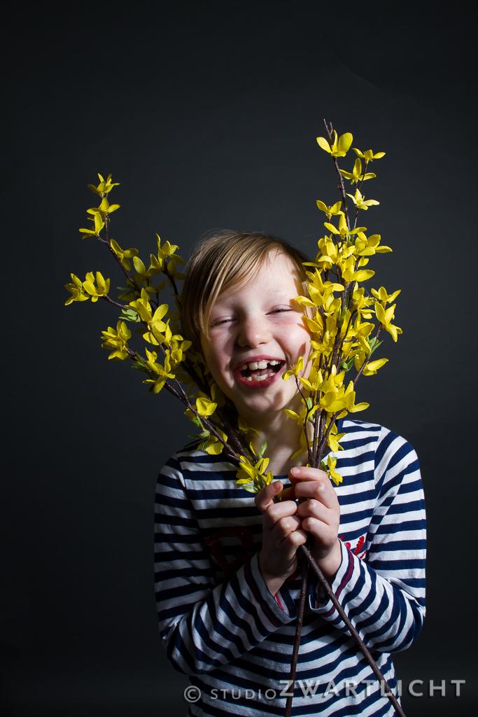 vrolijk studioportret met gele bloemen