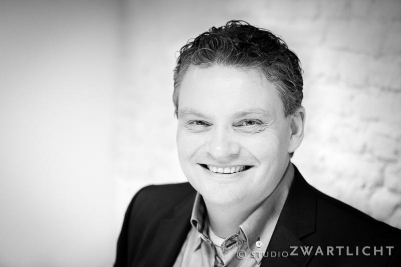 zwart-wit zakelijk portret lachende man bij witte muur